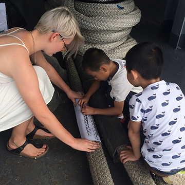 Anastasiia Palamarchuk making art from ship's rope with children