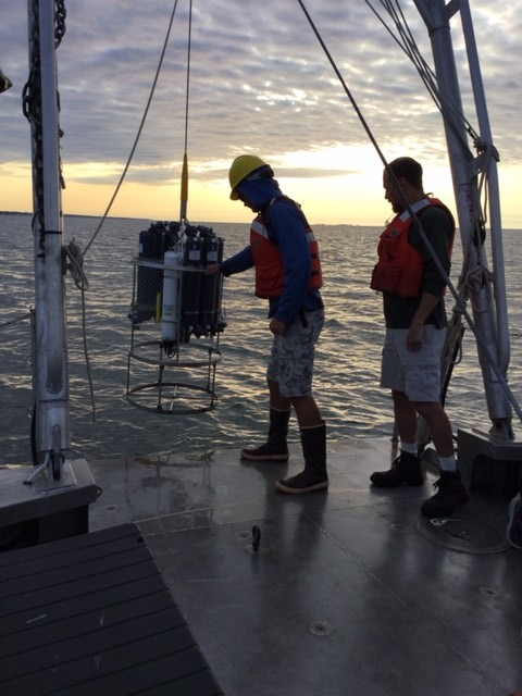 A rosette holder for Niskin bottles is lowered into Long Island Sound to collect water samples.