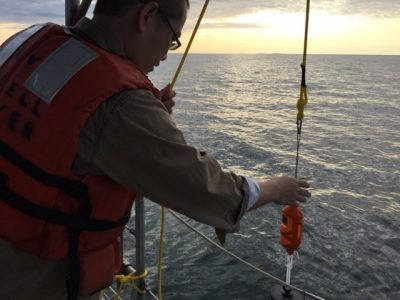 Marine sciences graduate student Yan Ji lowers a CTD profiler into the waters of Long Island Sound during an Aug. 24 research cruise.