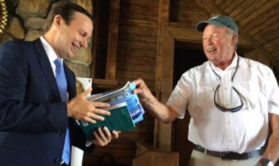 Sen. Christopher Murphy, left, receives a book about Long Island Sound from UConn marine sciences Prof. Charles Yarish at an event in Greenwich in August 2017.