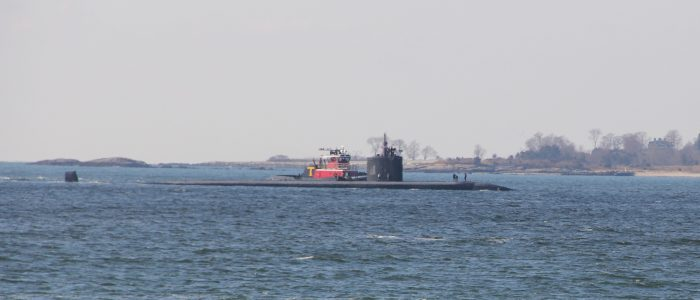 A nuclear-powered submarine accompanied by a tug boat enters the Thames River, just offshore from CT Sea Grant offices, on Dec. 11, heading for the Naval base in Groton.