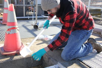 Jake Madden collects a water sample at the Mystic Wastewater Treatment Plant that for a testing project that could open areas to shellfish farming.