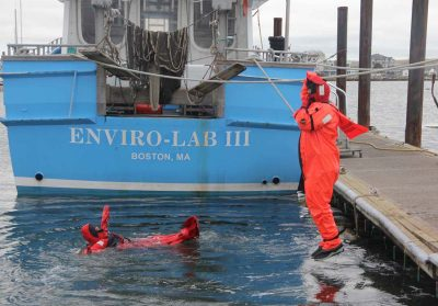 Fishermen jump into the water to practice using their immersion suits.