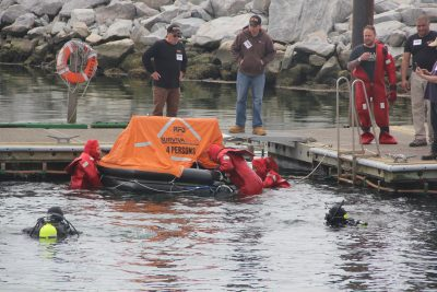 Fishermen climb into a life raft in their immersion suits during safety & survival training. Photo: Judy Benson / Connecticut Sea Grant