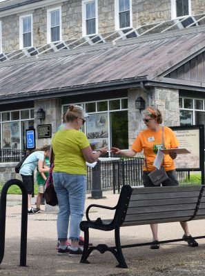 Judy Benson of Connecticut Sea Grant, right, hands out a Quest booklet at Fort Trumbull.