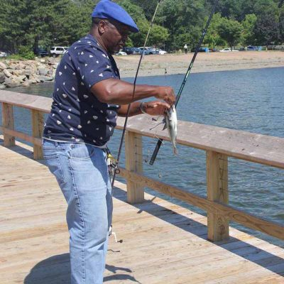Andre Craig of New Haven unhooks a porgy he caught off the pier at Fort Hale Park at the mouth of the Quinnipiac River on the city's east side.