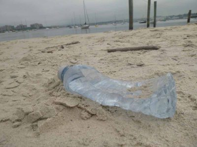An empty water bottle lies on a Long Island Sound beach
