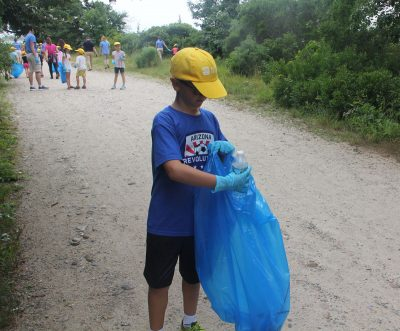 Alex Mynuk deposits an empty water bottle he found off the main trail at Bluff Point into a trash bag.