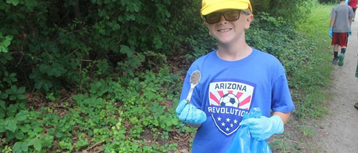 Mystic Aquarium summer camper Alex Mynuk shows a plastic spoon he collected during a clean-up at Bluff Point State Park to launch the #DontTrashLISound campaign.