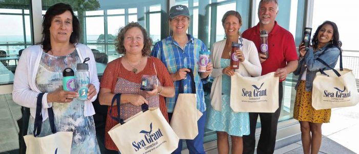 """CT Sea Grant staff show reusable water bottles and mugs with """"Break the single-use plastic habit"""" stickers that are part of the Please #DontTrashLISound campaign."""