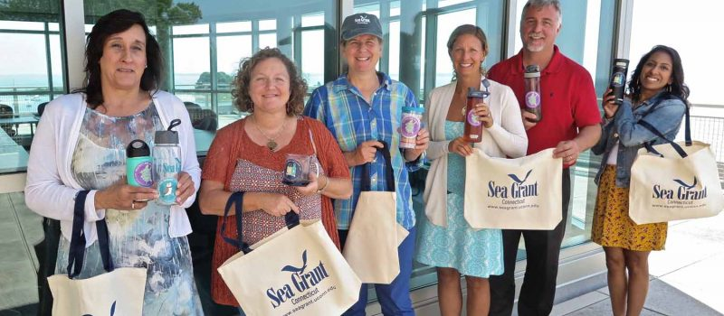 "CT Sea Grant staff show reusable water bottles and mugs with ""Break the single-use plastic habit"" stickers that are part of the Please #DontTrashLISound campaign."