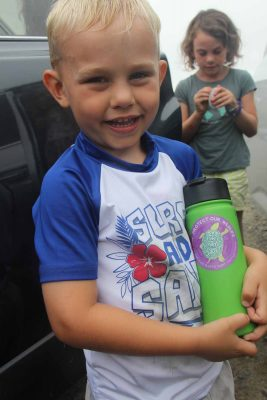 "William Aspinwall shows the ""Protect Our Wildlife: Break the Single-Use Plastic Habit"" sticker on his water bottle after he and his family picked up trash at Bluff Point State Park on Aug. 1."