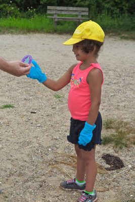 Mystic Aquarium summer camper Athena Costick, 5, receives one of the stickers being given out as part of the #DontTrashLISound campaign.