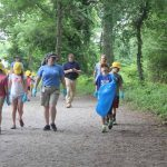 Mystic Aquarium summer campers head out on the main trail at Bluff Point State Park with trash bags and gloves to pick up trash.