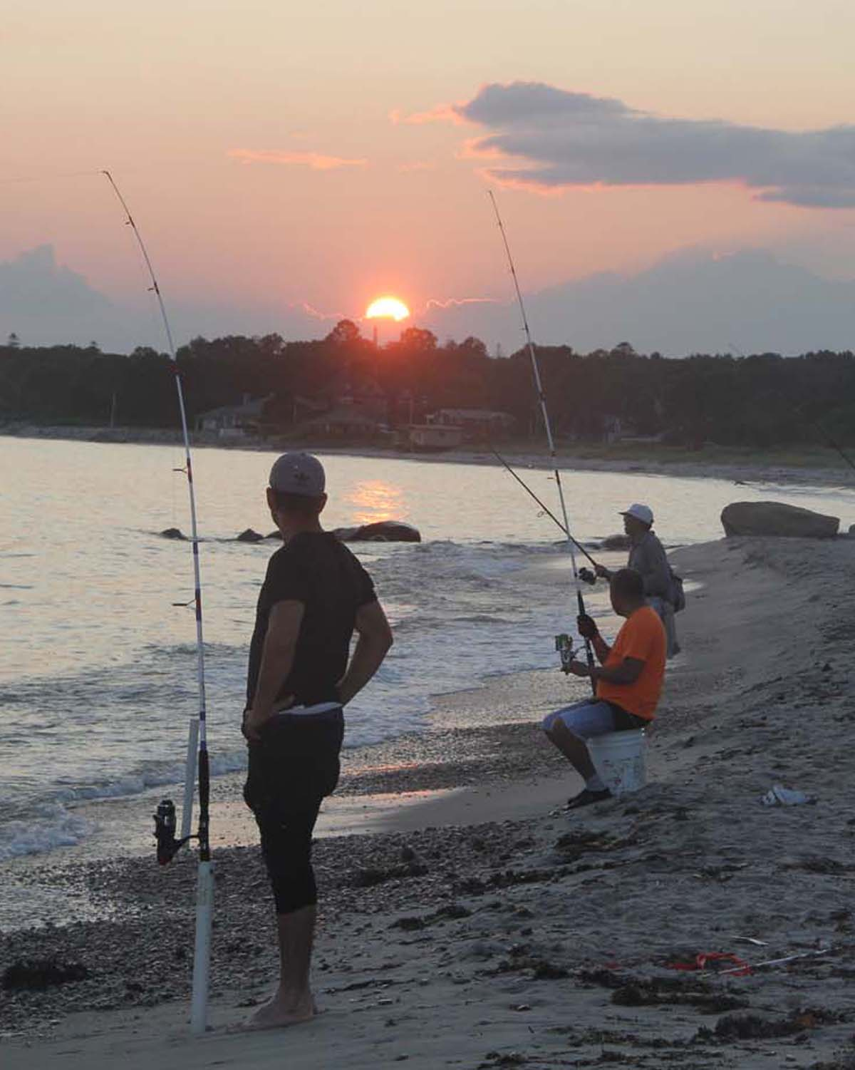 Fishermen with surf-casting poles watch the setting sun from the beach at Harkness Memorial State Park in Waterford on Aug. 22.