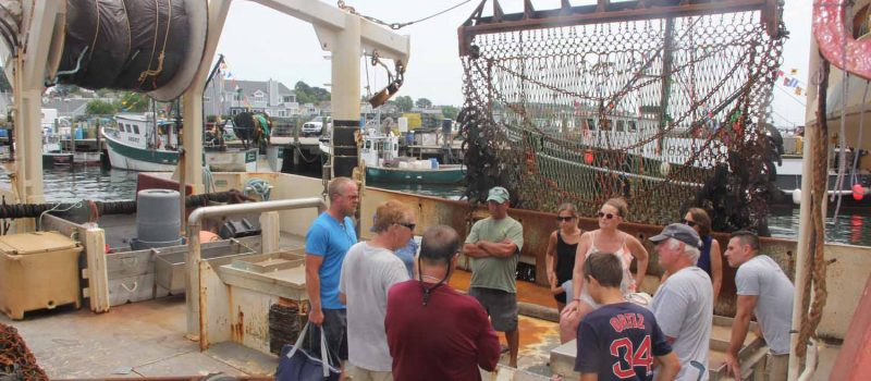 Joe Gilbert, second from right, tells a group of visitors about his scallop fishing vessel during an open house at Stonington Town Dock on July 28.