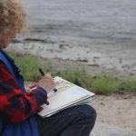 Mary Horrigan of Marlborough painted with water colors near a small sandy beach next the the Marine Sciences Building.