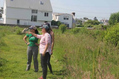 Juliana Barrett talks with student volunteers helping with a restoration project at Dodge Paddock, a coastal preserve in Stonington, last summer.