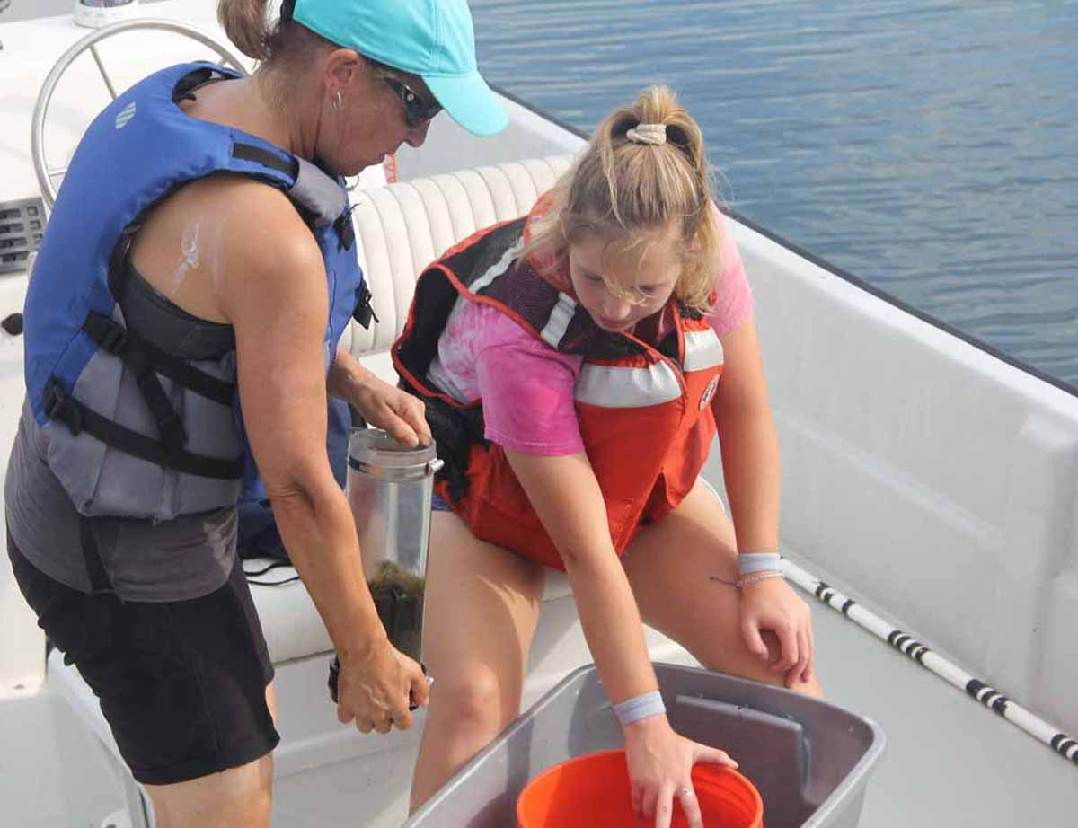 Claudia Koerting, left, academic assistant in marine sciences, takes a sample collected in Little Narragansett Bay from UConn student Mia Dupuis.