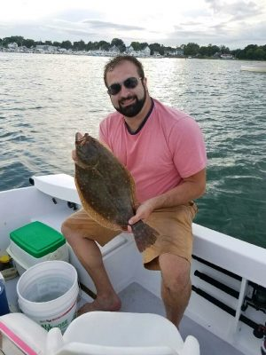 Dan Bergeron shows a summer flounder he caugh tthis summer in Niantic Bay while fishing with his father Roy, who took the photo.