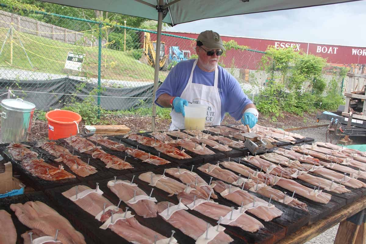 An Essex Rotary Club volunteer adds a special seasoning sauce to shad fillets about to be grilled at the annual Shad Bake at the Connecticut River Museum in June.