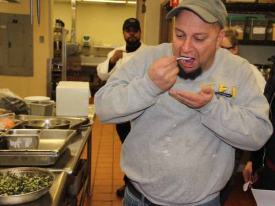 Chris Szewczyk, owner of Taino Smokehouse in Middletown, samples some of the kelp and leek topping for the salmon dish prepared by chef Jeff Trombetta.