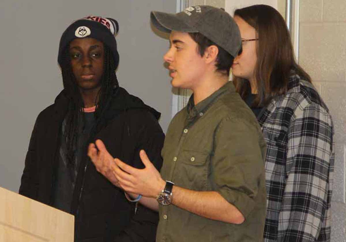 Liam Nagle, center, describes how hospitals, schools and other critical facilities in Miami Beach would be impacted for a four-foot rise in sea level as team members Florence Opoku, left, and Sara Schechter, await their turn for their portions of the presentation.