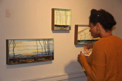 "UConn student Annalisa Mudahy looks at three paper, metal and clay works created by artist Ashby Carlisle, ""On a Clear Day,"" left; ""Whispers in the March,"" center; and ""On Shore Breeze,"" right."