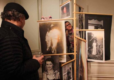 """Attendees at the opening of """"Crosscurrents"""" learn about women who went to sea in """"A Further Sea"""" and """"Seafaring Women"""" exhibits created by Anastasiia Raina and Rebecca Sittler."""