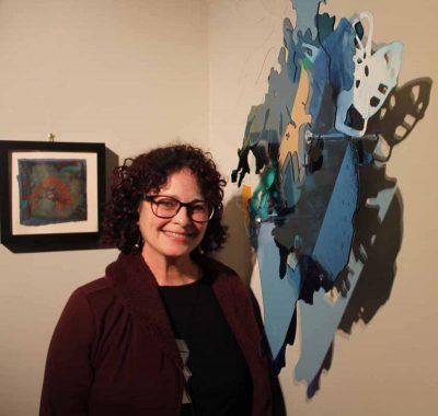 """Artist Deborah Hesse stands beside her work, """"Swish, Specimen 2.2,"""" during the opening of """"Crosscurrents."""""""