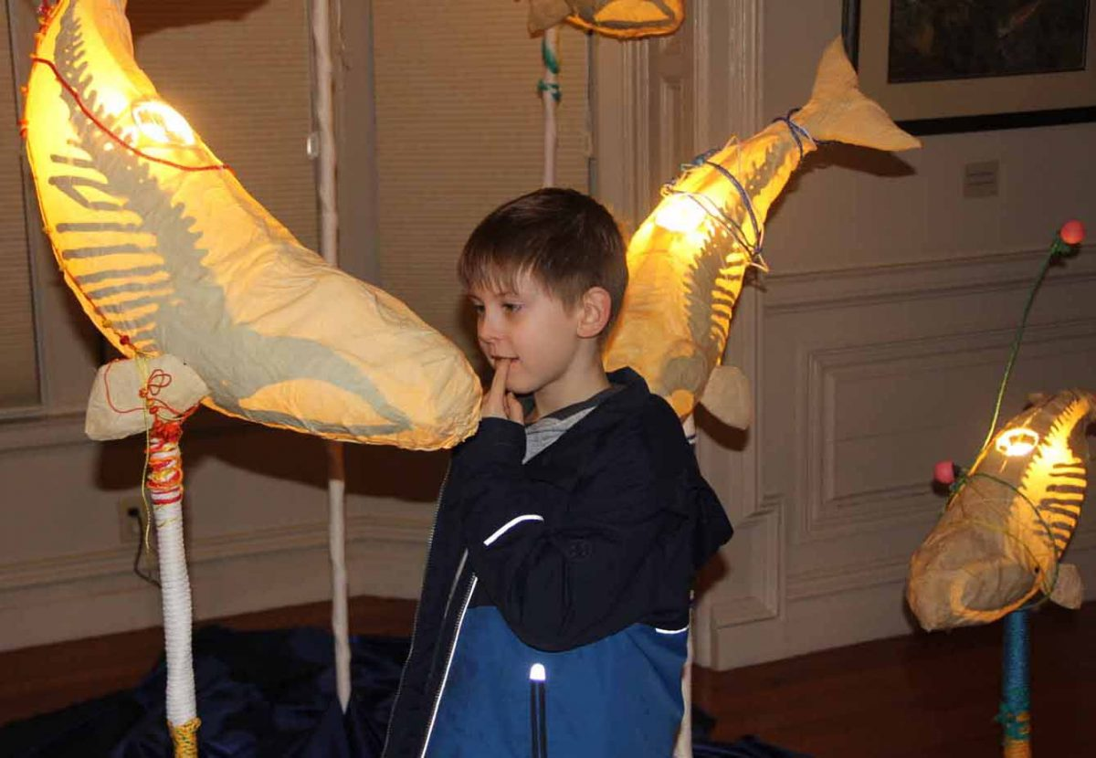 """Chancellor Talbot, 8, of East Lyme, looks at one of the """"Ghost Whales"""" created by Kristian Brevik that is part of the """"Crosscurrents"""" exhibit of CT Sea Grant Arts Support Awards program during the opening on Jan. 24."""