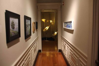 "Scenes of the Avery Point campus done by members of the Connecticut Plein Air Painters Society are hung in a hallway leading to the room where ""Ghost Whales,"" a work by Kristian Brevik, is displayed."