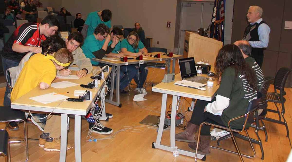The team from the Science and Technology Magnet High School of Southeastern Connecticut, left, competed against the team from Cogichaug Regional High School in the final round of the 22nd Annual Quahog Bowl. Standing is Evan Ward, science judge for the competition and head of the UConn Marine Sciences Department.