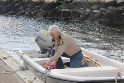 Richard Conant, deputy shellfish warden for Groton, checks the fuel in the boat he uses to collect water samples from the town's recreational shellfishing beds.