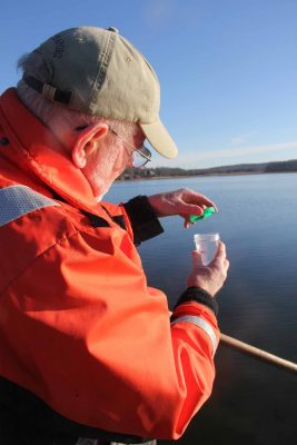 Don Murphy, chairman of the Stonington Shellfish Commission, places a cap onto a newly collected water sample from a shellfishing area in the Mystic River.