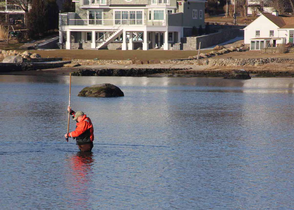 Don Murphy, chairman of the Stonington Shellfish Commission, lifts a water sample from one of the town's recreational shellfishing areas in the Mystic River at low tide on March 13.