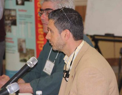 Michael Pacucilla, director of health for the East Shore District Health Department, talks about West Nile virus during a panel discussion. Behind him is University of Rhode Island Prof. Jose Amador.