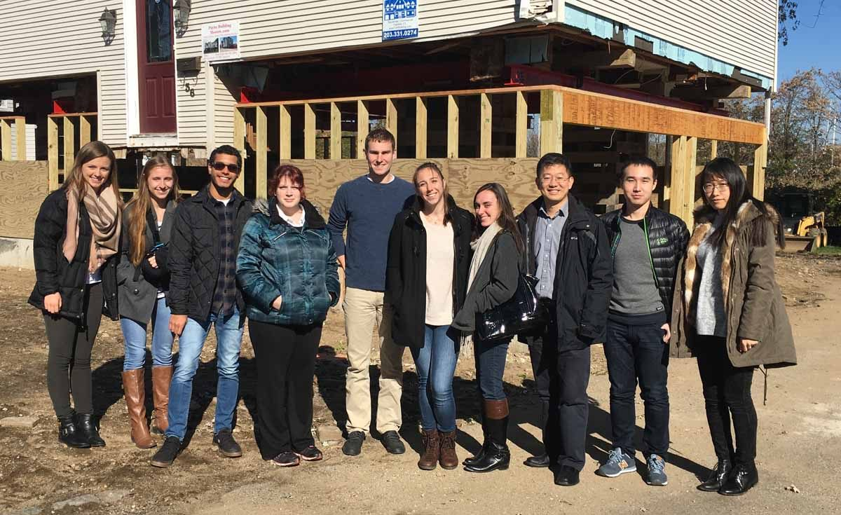 Prof. Wei Zhang, third from right, used this home being elevated in Fairfield as part of his research project. With him are several UConn graduate students, including three who worked on the project.