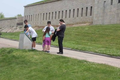 Participants look for clues on one of the interpretive signs at Fort Trumbull.