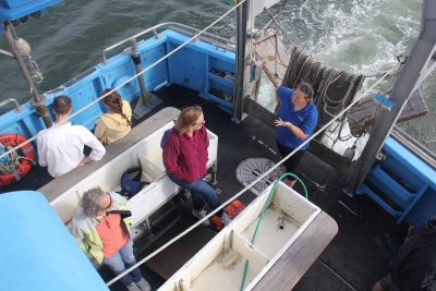 A Project Oceanology crew member answers a question from one of the passengers as the vessel approaches the docks at Avery Point.