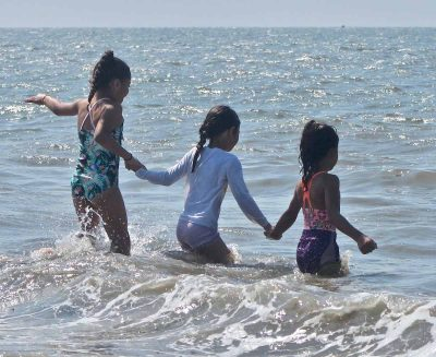 Three girls from the New Britain YWCA summer camp enjoy the waves at Lighthouse Point Park.