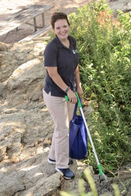 MaryEllen Mateleska, director of education and conservation at Mystic Aquarium, uses a trash picker and a reusable bag to gather trash at Lighthouse Point Park.
