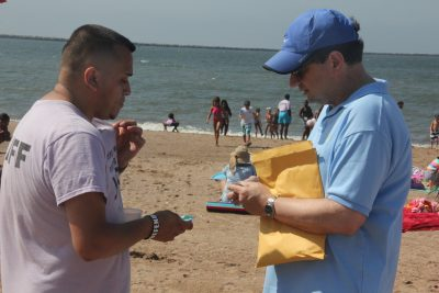 Robert Burg, right, communications coordinator for the Long Island Sound Study, gives Protect Our Wildlife stickers to YWCA summer camp teacher Justin Del Rio for the campers.