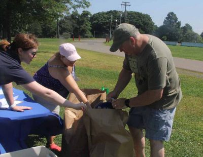Volunteer Scott Shail, right, empties the trash he collected into a large paper bag as his wife Laura, Sunny Valley Preserve administrator for The Nature Consevancy, and Ireland Wilson, senior conservation instructor for the Mystic Aquarium, help hold the bag.