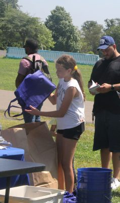 Courtney Ratti, 11, empties trash she collected during the cleanup into a large bag.