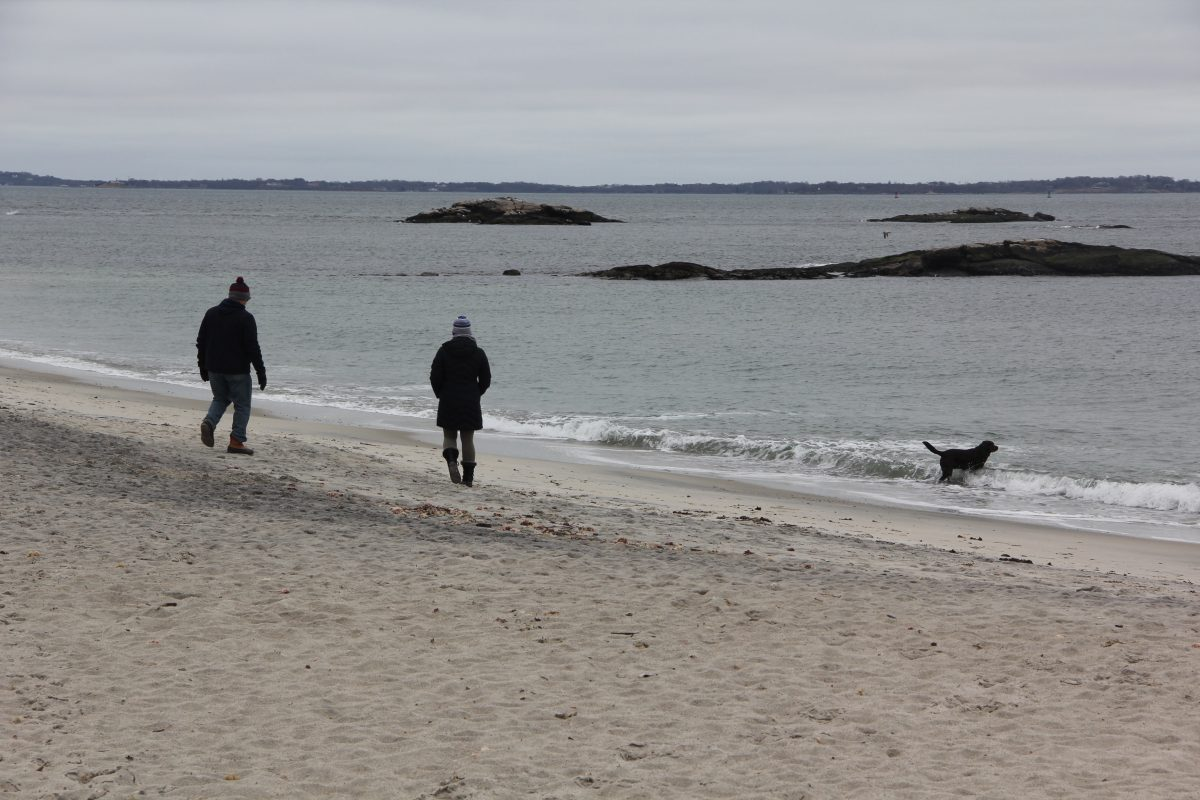 A couple enjoy a walk with their dog at Waterford Town Beach on Thursday.