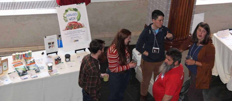 Participants in the National Seaweed Symposium gather near one of the exhibits at the Seaweed Showcase on the second day of the event.