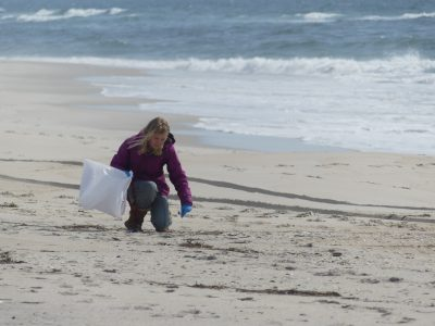 A participant in balloon debris survey collects trash at Jones Beach.