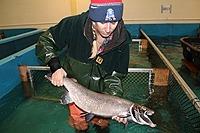 Woman holding salmon.