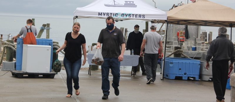 Customers leave with oysters and lobsters purchased on May 23 at the new direct sales market at the Noank Aquaculture Cooperative.